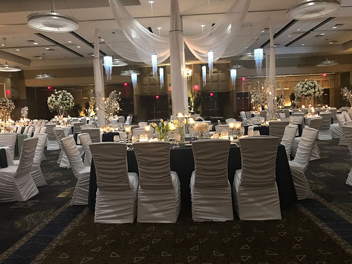 View of wedding gallery -  Conference center decorated in white with fabric chairs in foreground