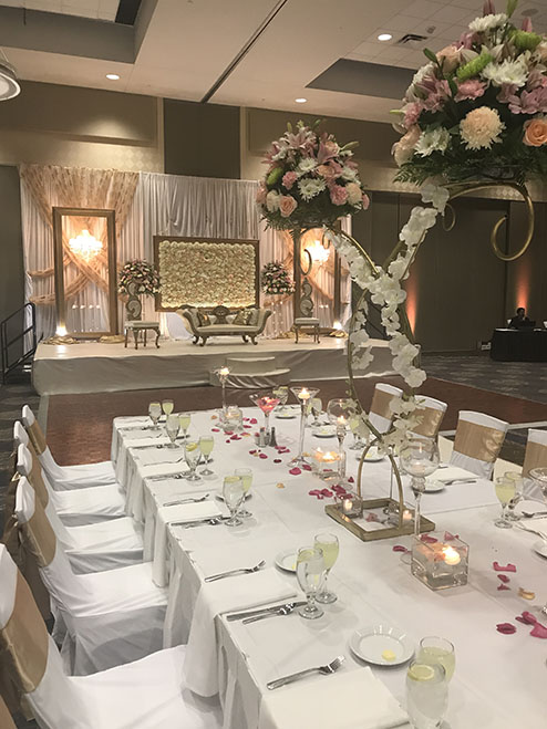 View of wedding gallery - White table cloth decorated long table and view of the stage