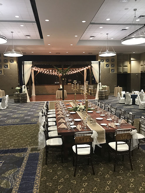 View of wedding gallery - Long table with string lights and a rustic decor