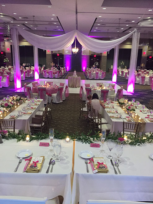 View of wedding gallery -  Conference center decorated in white fabric and purple lighting