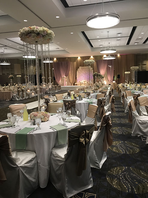 View of wedding gallery -  Conference center decorated in white with fabric chairs and flower decor
