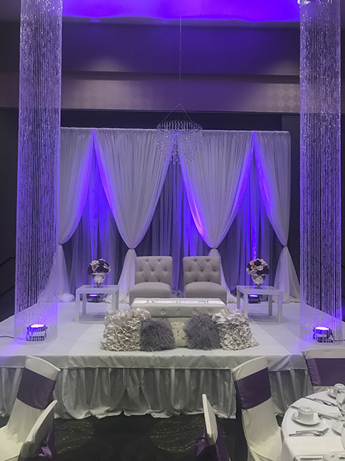 View of wedding gallery - Stage decorated with white fabric lit up by purple lights