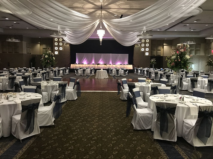 View of wedding gallery - View of stage and circular tables from the back of the room