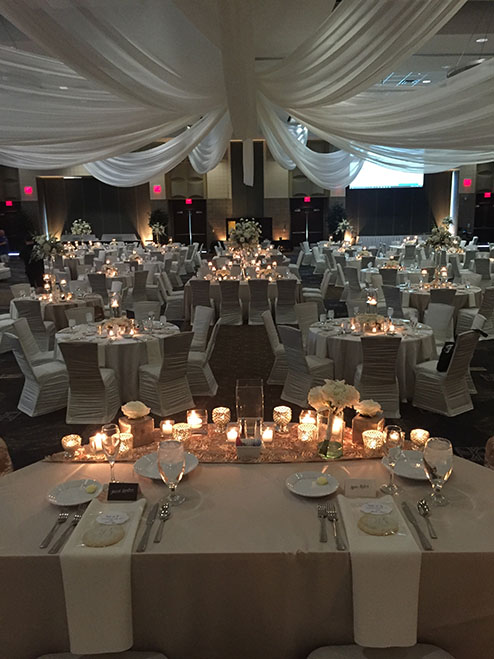 View of wedding gallery - Candles on table with draped fabric over the ceiling