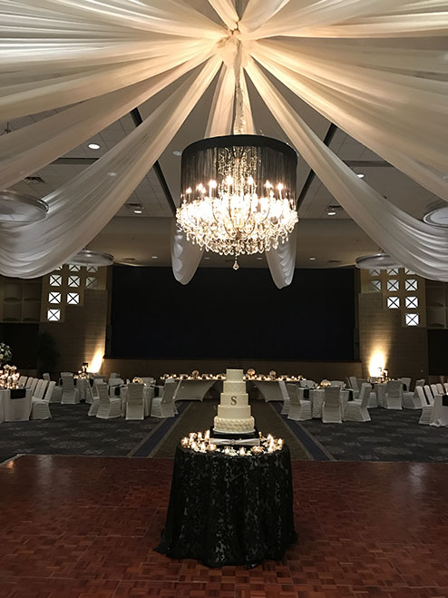 View of wedding gallery - chandelier and cake on a circular table