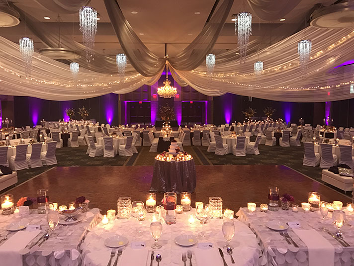 View of wedding gallery -  Conference center decorated in white with a long table and with purple lighting